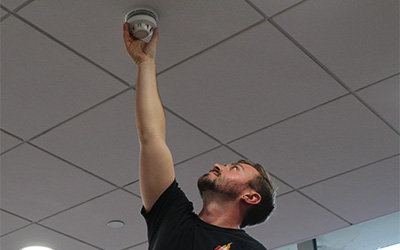 fire alarms man installing fire alarm on ceiling