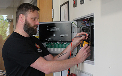 fire alarms service and maintenance man testing panel